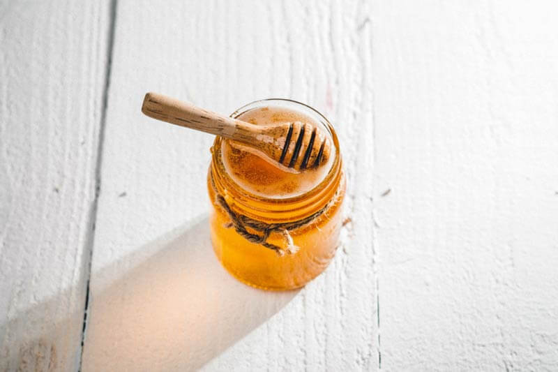 Jar of honey sitting on a table