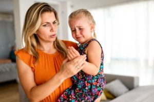 Mother comforting her crying child who had allergic reaction to bee sting, can allergies go away?