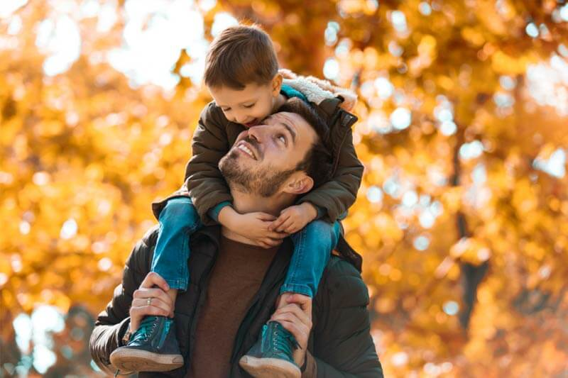 Child on shoulders of father