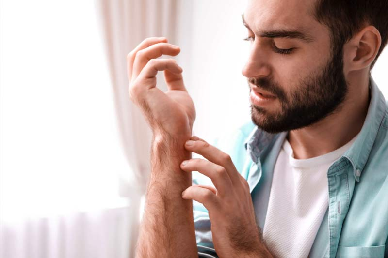 Man scratching his arm wondering if bee stings get worse each time